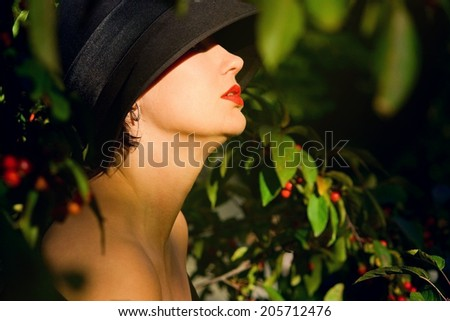 Head shod portrait of a beautiful woman in her forties sitting profile in black hat with her bare shoulders and neck in sun beat, green foliage, summer, autumn. Selective focus