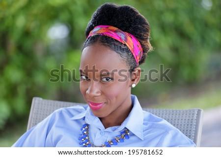 Head shot of a beautiful Jamaicn woman smiling - stock photo