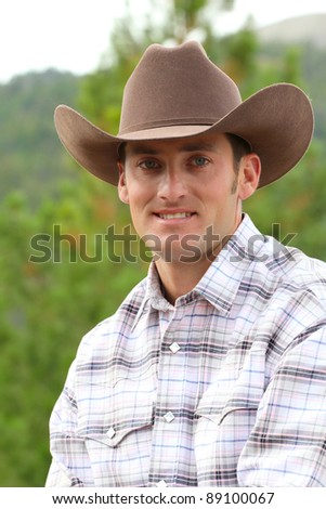 Head shot of a cowboy outside in the field - stock photo