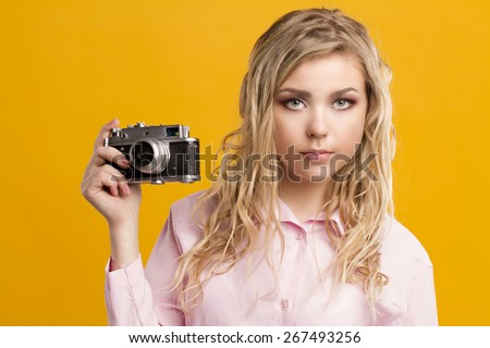 Head shot of a pretty pin-up girl holding a vintage camera. - stock photo