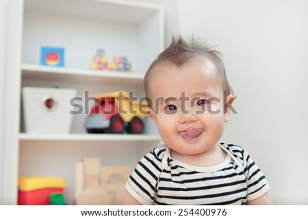 Head shot of a silly baby sticking his tongue out. - stock photo