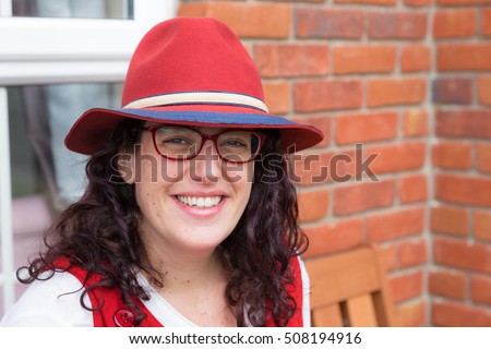 Head shot of a woman with glasses wearing a red dress and hat with a big smile sitting in front of her house