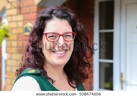 Head shot of a young woman with a big smile wearing glasses and a green dress standing in front of her house