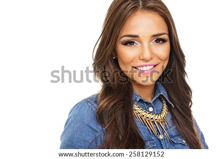 Head shot of gorgeous modern young Latina Caucasian brunette woman smiling. Beautiful girl in blue denim shirt and modern golden necklace posing happy isolated on white background.Retouched,copy space - stock photo