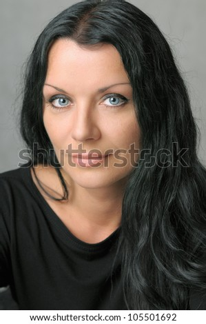 Head shot of mid age brunette woman with light smile - stock photo