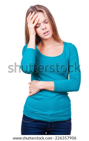 Headache. Depressed young woman touching her head with hand while standing isolated on white - stock photo