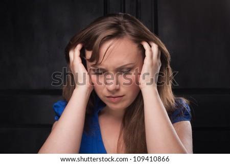 Headache. Girl clasped head in her hands. Close-up. Dark background. - stock photo