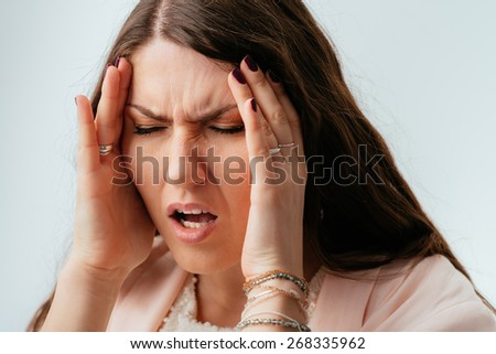 Headache,long-haired beautiful brunette girl pain in temples - stock photo
