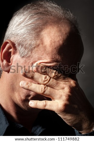 Headache. Portrait of an elderly man with face closed by hand - stock photo