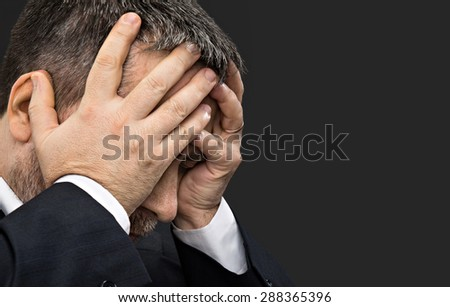 Headache. Portrait of an elderly man with face closed by hands on dark background with copy-space - stock photo
