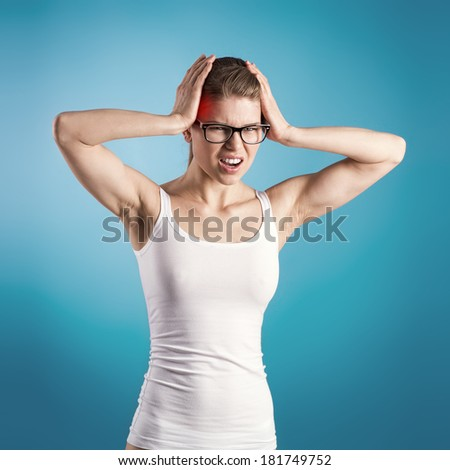 Headache. Portrait of young Caucasian woman shouting in pain over blue background.  - stock photo