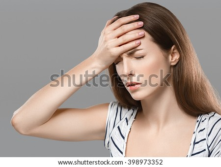Headaches Beautiful young woman with headache touching her head  - stock photo