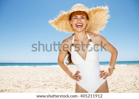 Heading to white sand blue sea paradise. Portrait of happy woman in white swimsuit and straw hat at sandy beach on a sunny day - stock photo