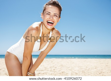 Heading to white sand blue sea paradise. Portrait of smiling woman in white swimsuit at sandy beach on a sunny day - stock photo