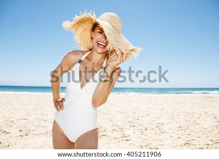 Heading to white sand blue sea paradise. Smiling woman in white swimsuit hiding in big straw hat at sandy beach on a sunny day - stock photo
