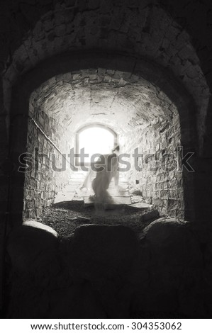 Headless ghost trying to get away from the light in medieval castle. - stock photo