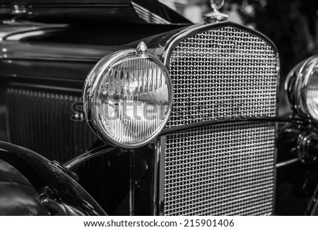 Headlight and grill of vintage automobile in black and white. - stock photo