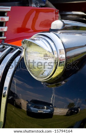 headlight in vintage american red and black car front - stock photo