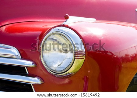 headlight in vintage american red car front - stock photo