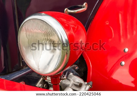 Headlight of a red old-timer - stock photo