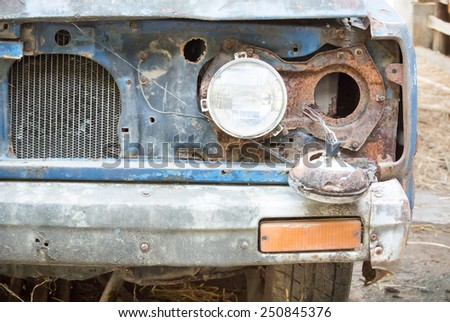 Headlight of  an old and damaged blue vehicle