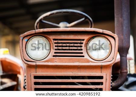 headlight rusty vintage farm tractor - stock photo