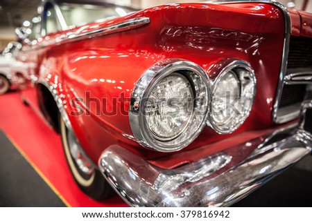 Headlights of a red vintage car in a salon - stock photo