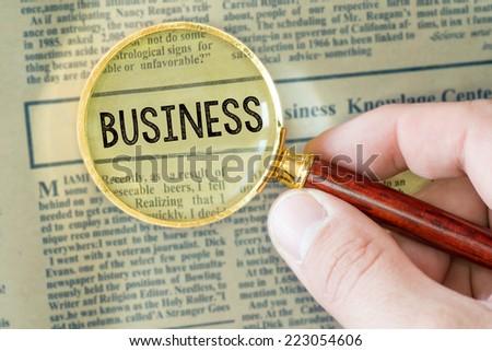 Headline of newspaper through magnifier. Headline of newspaper through magnifying glass, with Business word  - stock photo