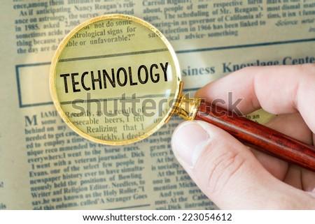 Headline of newspaper through magnifier. Headline of newspaper through magnifying glass, with Technology word  - stock photo