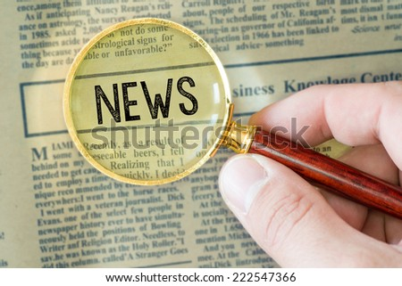 Headline of newspaper through magnifying glass, with News word - stock photo
