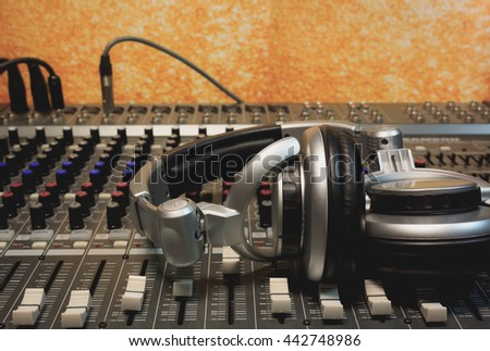 headphone on sound mixer dj with gold bokeh background. - stock photo
