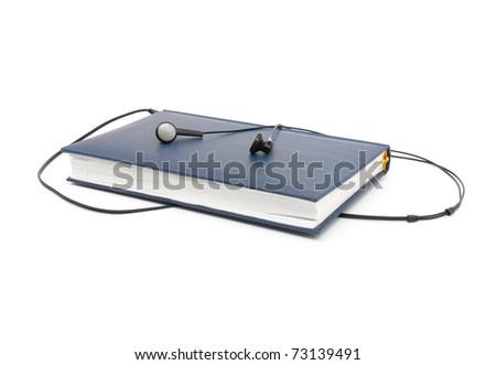 headphones and blue book (audio book concept) - stock photo