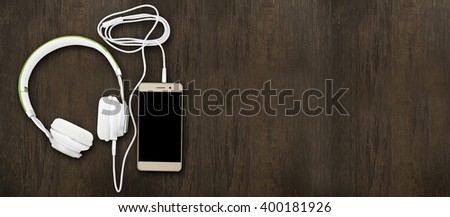 headphones and gold mobile smartphone on wood with copy space