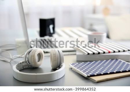 Headphones and laptop on white table against defocused background - stock photo