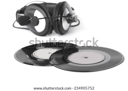 headphones arranged over some old 45 rpm records - stock photo
