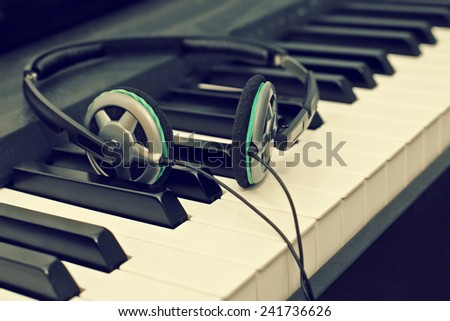 Headphones lying on the piano keys - stock photo