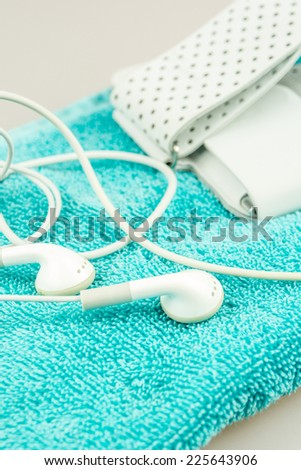 headphones, mp3 player and turquise  towel symbols of modern lifestyle, sport, fitness, activities