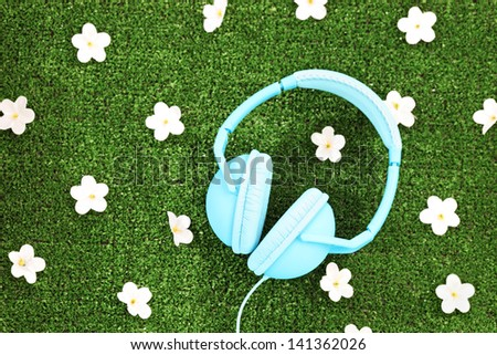 Headphones on a green grass with daisy flowers