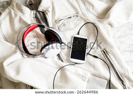 Headphones on a white Jacket. Ready to go out.  - stock photo