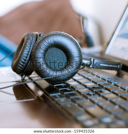 headphones on notebook after music mixing - stock photo