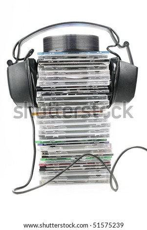 headphones on stack of disks on white background - stock photo
