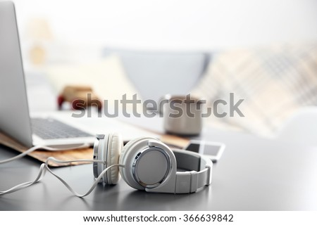 Headphones, phone and laptop on white table against defocused background - stock photo