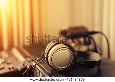 Headphones with amplifier on table, with copy space, soft focus, vintage tone - stock photo