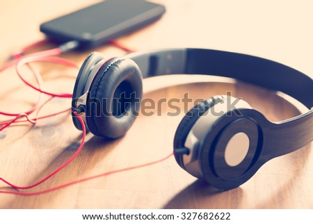 headphones with cellphone on wooden table - stock photo