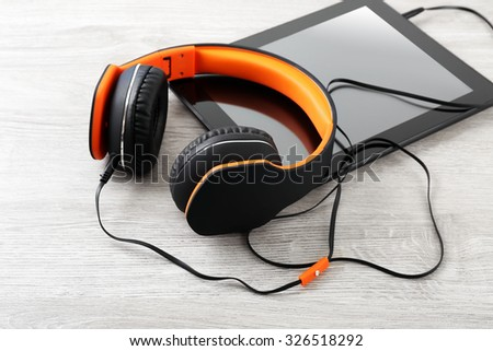 Headphones with tablet on wooden table close up - stock photo