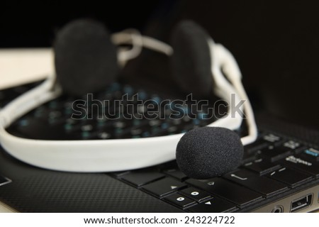 Headset on laptop - Black and white headphones with microphone lie on keyboard close up - stock photo