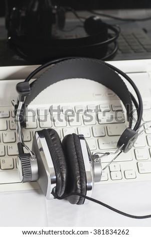 Headset on laptop computer keyboard.Communication concept - stock photo