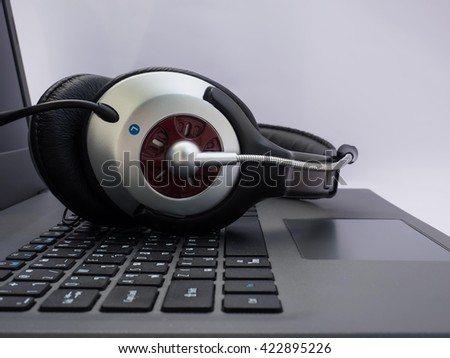 headset on laptop computer keyboard concept for communication  it support