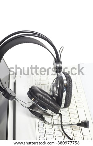 Headset on laptop computer keyboard isolated on white.Communication concept - stock photo