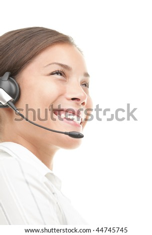 Headset woman smiling very kindly. Closeup of beautiful young mixed race chinese / caucasian secretary / assistant speaking with headphones while working in call center. Isolated on white background. - stock photo